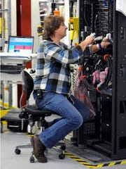 """Louis deOlde, of New Paltz, an IBM employee for 36 years, works on the assembly of an zEnterprise BC12 server on the Systems Assembly Test floor in building 052 at the Poughkeepsie main plant. The designation BC12 and EC12 are IBM's most current mainframe computers, with """"BC"""" standing for Business Class and """"EC"""" standing for Enterprise Class – the higher end of the two."""