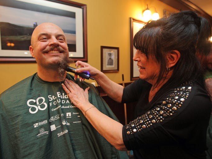 Penny DeMartino shaves Jeremy Pratt's mustache during the St. BaldrickÕs Foundation eighth annual fundraiser for childhood cancer research at Claddagh Bar and Grill in Mahopac on March 29, 2014.
