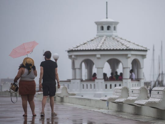 A couple is caught in the wind as people huddle under a mirador to escape the rain on Friday, July 6, 2018.