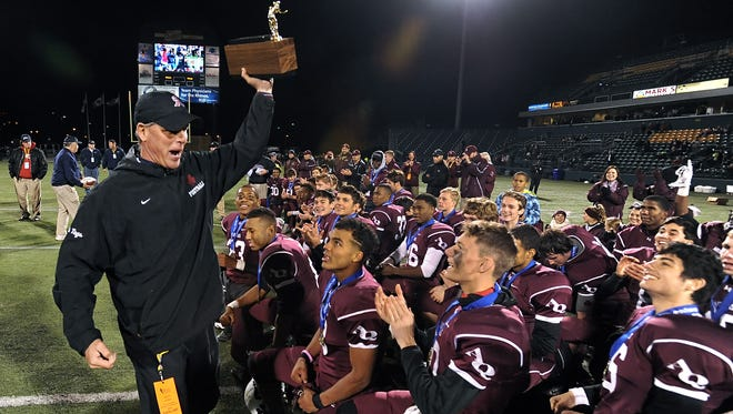 Aquinas head coach Chris Battaglia hoists the Section V Class AA football trophy on Sunday. The Little Irish have won a sectional title in football nine of the past 10 years and superintendents in Monroe County schools want the state to consider whether private schools should be allowed to play in public school tournaments.