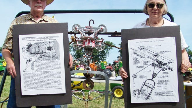 With a F.E. Myers hay trolley set up behind them, John and Joan Brusoe display some of the informational material for one of the types of equipment that was once standard on farms for moving hay from wagons into mows.