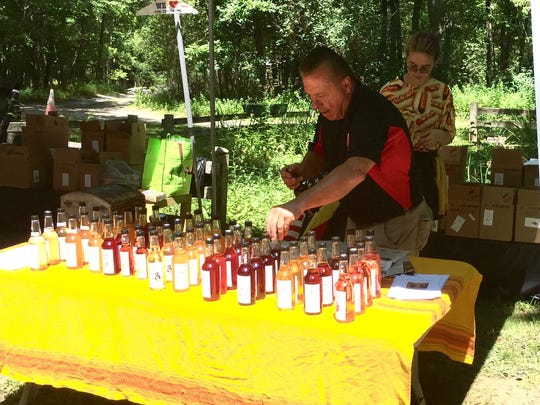 Volunteer Ray Patchey arranges bottles, as Katie Brower, 16 of Red Hook, assists, at the annual vinegar festival at Our Lady of the Resurrection Monastery in the Town of Union Vale Sunday.