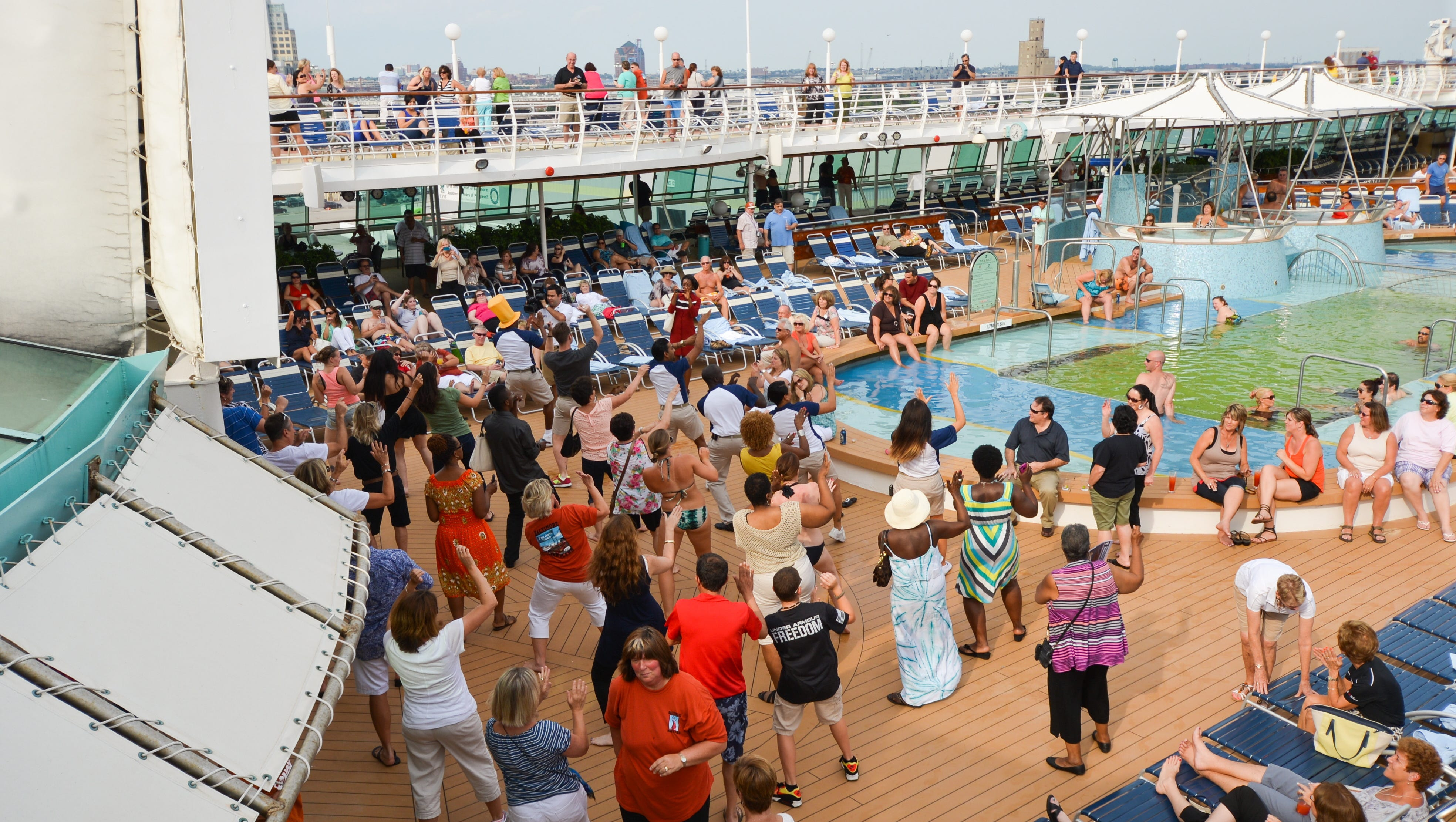 Grandeur of the Seas' entertainment staff gets passengers hopping during a sailaway party with line dancing next to the pool.