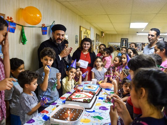 """Father Andrew Mahrous, of St. Mary and St. Mercurious Coptic Orthodox Church in Conshohocken, leads the singing of the """"Happy Birthday"""" song during a July birthday celebration for Coptic children at St. Mary's Catholic Church in York."""