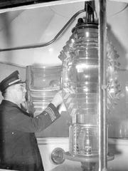 Belle Isle Lighthouse keeper Capt. Ernest J. Bondy inspects the lens in 1937.