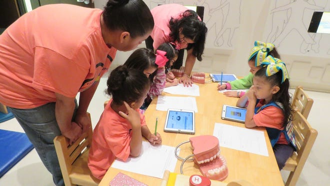 Members of Daisy Troop 9684 use iPads to learn about pet care.