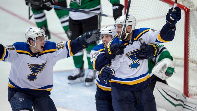 St. Louis Blues center David Backes (42) and left wing Jaden Schwartz (17) and St. Louis Blues right wing Vladimir Tarasenko (91) celebrate Backes scoring the game winning goal against Dallas Stars goalie Antti Niemi (31) during the overtime period in game two.