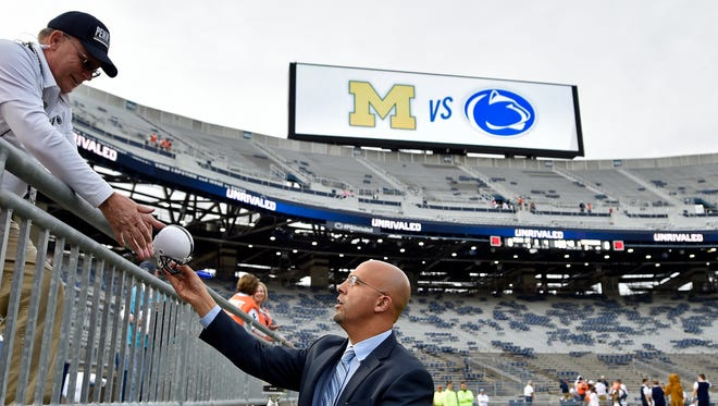 Penn State head football coach James Franklin returns a souvenir helmet he autographed while greeting staff members inside Beaver Stadium before an NCAA Division I college football game Saturday, Oct. 21, 2017. The No. 2 Penn State Nittany Lions host Michigan.