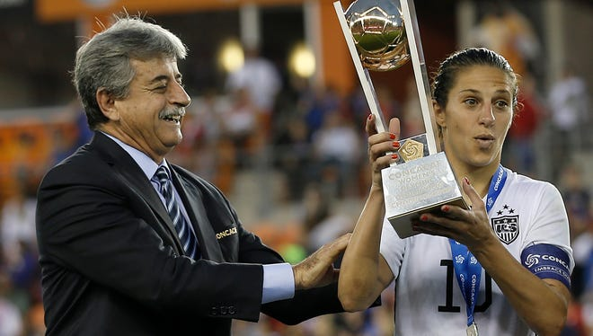 USA midfielder Carli Lloyd (10) is handed the championship trophy after USA defeated Canada in the 2016 CONCACAF women's Olympic soccer tournament at BBVA Compass Stadium. USA won 2 to 0.