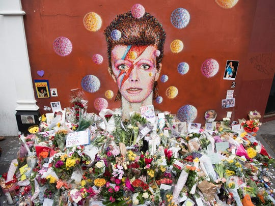 Floral tributes are seen beneath a London mural of David Bowie, painted by Australian street artist James Cochran the day after the announcement of Bowie's death.
