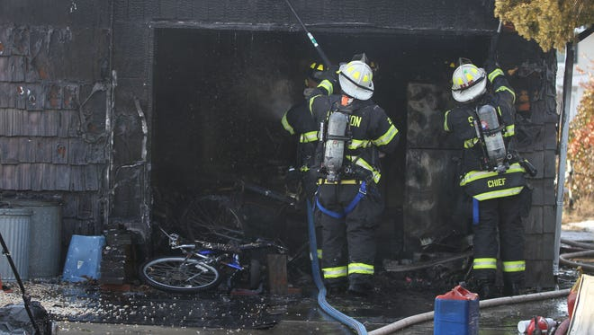 Brick Township firefighters check for additional hotspots in the garage at 46 East Pompano Drive Friday afternoon, February 10, 2017, after extinguishing a fire there.