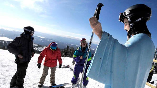 In this Feb. 20, 2011 file photo, University of Montana students, from left, Jake Coburn, Stephanie Ralls and Claire Dal Nogare, visit a statue of Jesus Christ at Whitefish Mountain Resort in Whitefish, Mont.