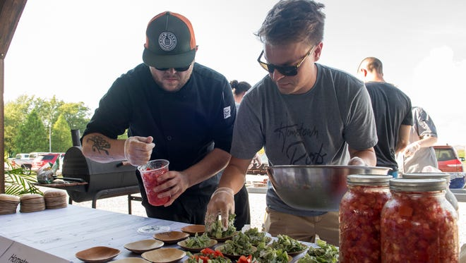 Josh West, left, and Hometown Roots owner Casey Todd, right, prepare salads during the Farm to Table event held at the Henderson County Fairgrounds Monday, July 16, 2018.