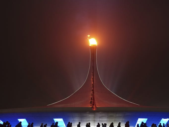 Spectators walk past the Olympic flame on a foggy night in Olympic Park during the 2014 Winter Olympics on Sunday, Feb. 16, 2014, in Sochi, Russia.
