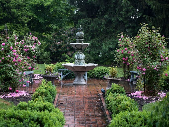 A fountain surrounded by roses and other plants inside