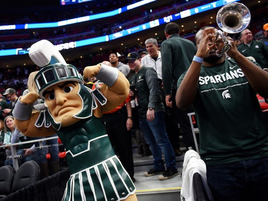 Michigan State mascot Sparty, left, flexes his muscles