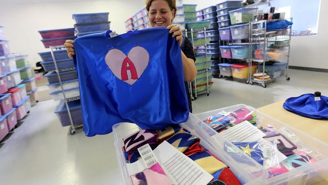 Holly Bartman, owner of Superfly Kids, shows off a custom-made children's cape at Super Fly Kids on Thursday, Sept.26, 2013, in Livonia, Mich.