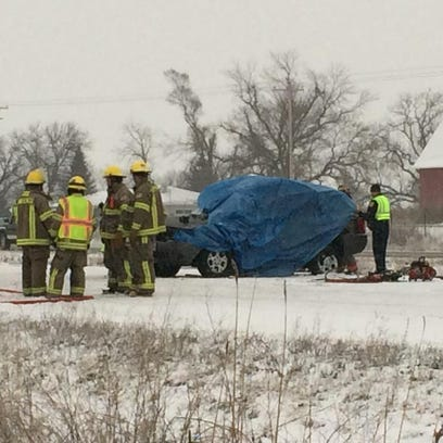 Emergency crews wrap a tarp around a vehicle involved