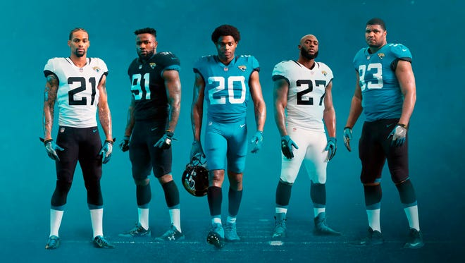 Jacksonville Jaguars players pose in new team uniforms, which were unveiled Thursday.