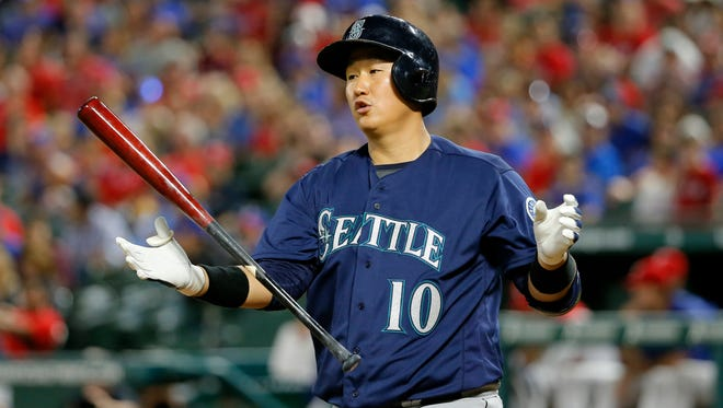 Seattle Mariners' Dae-Ho Lee of South Korea tosses his bat in the air after swinging at a pitch from Texas Rangers' Sam Dyson in the ninth inning of a baseball game on, Friday, June 3, 2016, in Arlington, Texas. Lee singled in the at-bat in the 7-3 Rangers win. (AP Photo/Tony Gutierrez)
