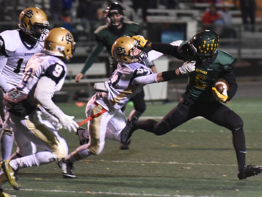 Groves running back Collin Heard (right) is tackled by Grosse Pointe South's Conor McKenna.