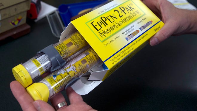 A pharmacist holds a package of EpiPen epinephrine auto-injector, a Mylan product.