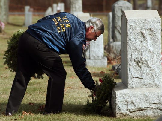 Bob Mederos of Ledgewood lays down a wreath as First Presbyterian and United Methodist Church of Succasunna join Wreaths Across America ensuring no veteran from Roxbury is forgotten during the holiday season. December 13, 2014. Succasunna, N.J. Bob Karp/Staff Photographer