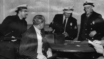December 28, 1951: Patrolman Edward Gugel, left, stands with a riot gun during the raid on the Merchants Club as Sgt. Jack Thiem confiscates money seized at the blackjack table.