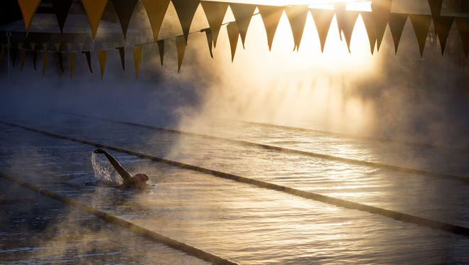 A member of the Marshall University swim team cuts through the rising steam, December 15, 2015, during practice at the Mona Plummer Aquatic Center. Marshall University, from Huntington, West Virginia, is holding an 11-day training camp at ASU. The temperature at the start of their 7 a.m. practice was 36 degrees; the water temperature is 80 degrees.