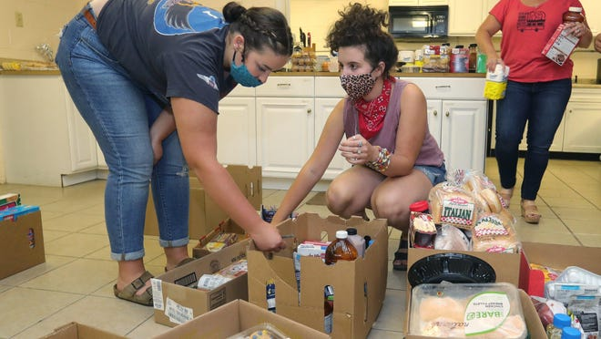 Charity Christian Church members, from left, Grace Farris, Lila Farris and Kellie Farris pack boxes of food last week as part of their Soup Wagon Relief outreach program.