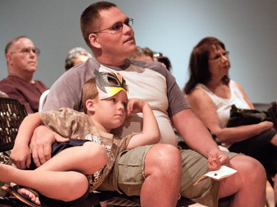 Zack Mickendrow, 6, sits with his father Christopher Mickendrow while listening to stories of La Llorona on Saturday during the La Llorona Festival at the Branigan Cultural Center.