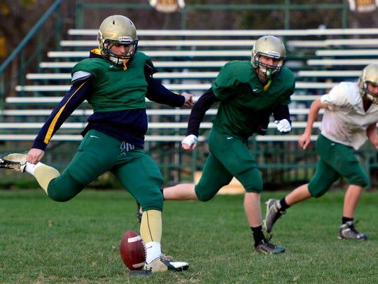 Luke Brennan kicks the ball during special teams practice