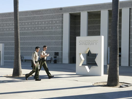 Two sheriff's deputies walk  past the Southwest Detention