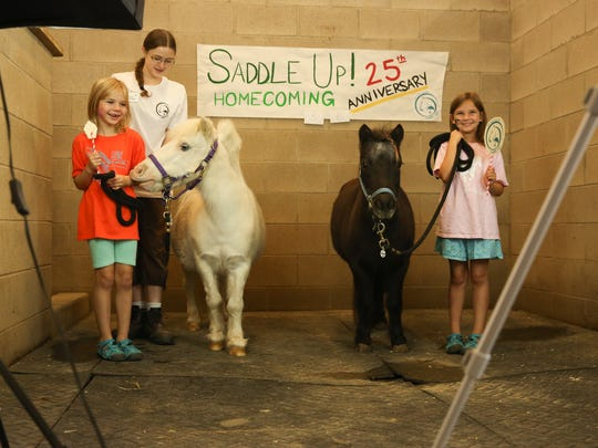 From left, Hannah Foster-Hoke stands with a Saddle