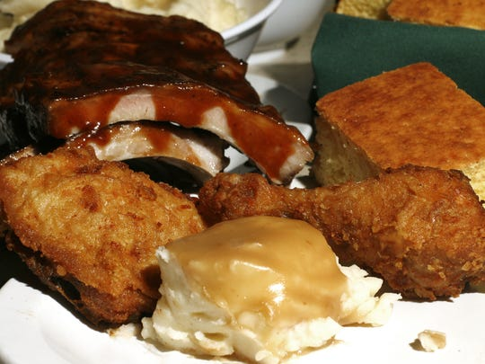 A Murph's Gaslight dinner consisting of fried chicken, mashed potatoes with gravy, cornbread and ribs.