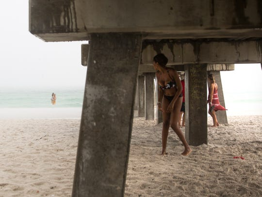 Ellen Greaves looks back at Edoardo Guida and Vittoria, 10, as she hides from the rain Monday, June 5, 2017, at the Naples Pier.