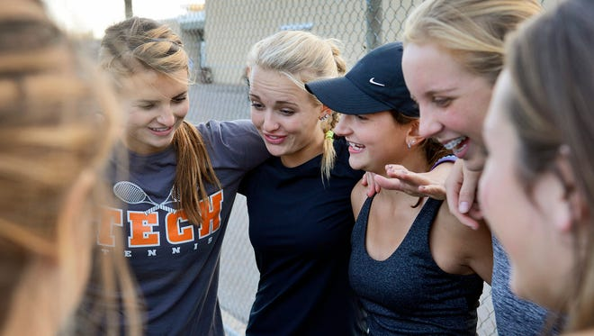 St. Cloud Tech's Ashley Tarrolly, in hat, links arms with her other sisters on the team, sophomore Katelyn, center, and junior Taylor, left center, as they rally with teammates at the close of practice Oct. 20, 2015, at South Junior High School.