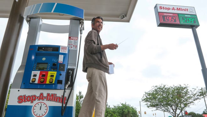 Joe Machado, district manager, uses a remote control to change the electronic sign with gas prices at the Stop-A-Minit at 4555 S.C. Highway 81 North in Anderson on Monday. The store opened in April.