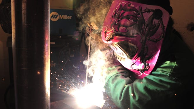 Butler Tech junior Alyssa Ashford on Wednesday welds pieces of metal together following a blue print. She decorated her welding mask with a pink rose and barbed wire. Teacher Shane McKinney says female welders are in high demand partly due to government projects requiring a certain number of female workers.