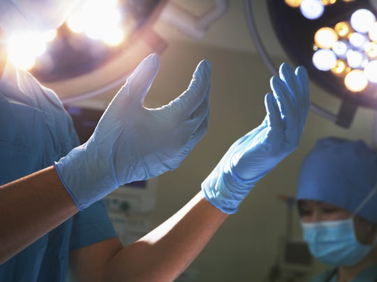 Hands in surgical gloves and lights