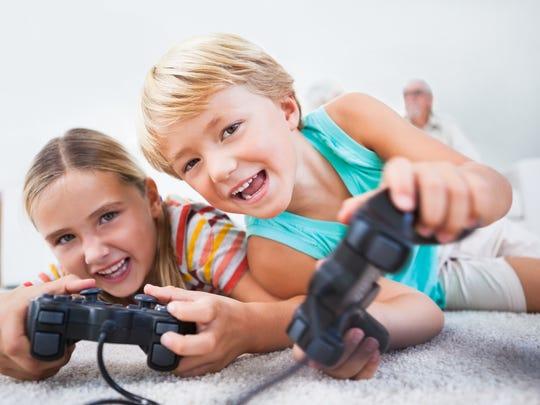 Siblings having fun playing video games.