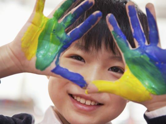 Portrait of smiling schoolboy finger painting, close