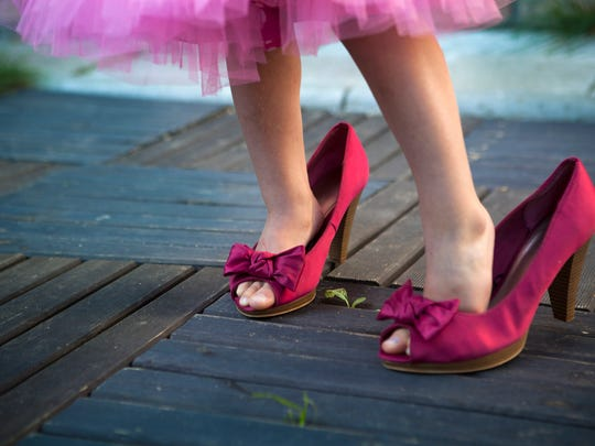 Little girl in her mother's high hells shoes
