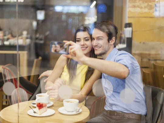 Couple taking selfie photo in cafe
