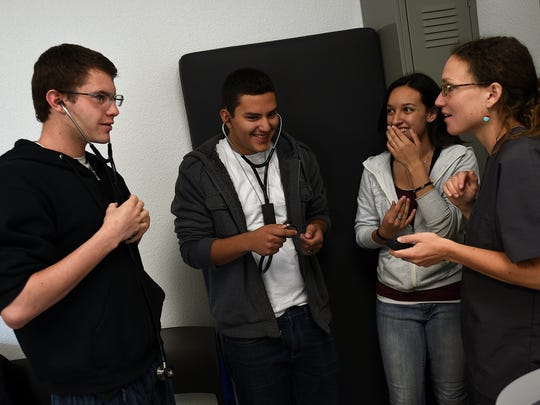 High school students, from left, Steven Dash, Eber Moreno and Joanna Silva listen to a simulated heart beat as current medical student Nikki Heidt, right, looks on during an open house tour of the University of Nevada Medical School in Reno on April 11, 2015.