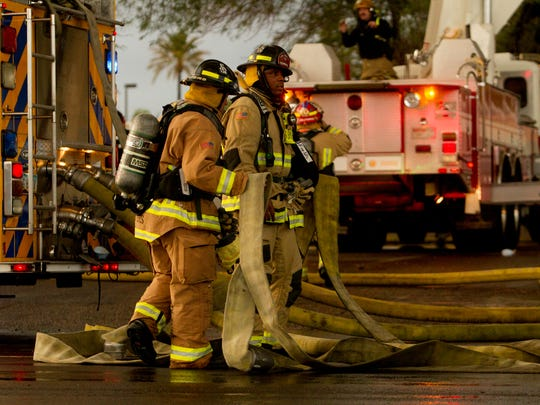 Phoenix firefighters roll out hoses on July 11, 2018,