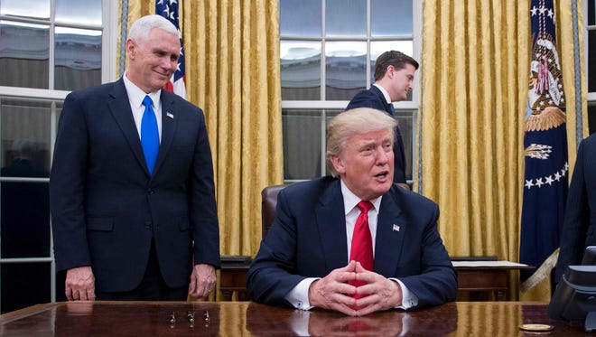 President Donald Trump (C) speaks to the press as he waits at his desk before signing conformations for General James Mattis as Secretary of Defense and General John Kelly as Secretary of Homeland Security, as Vice President Mike Pence looks on, in the Oval Office of the White House  in Washington, DC, January 20, 2017.