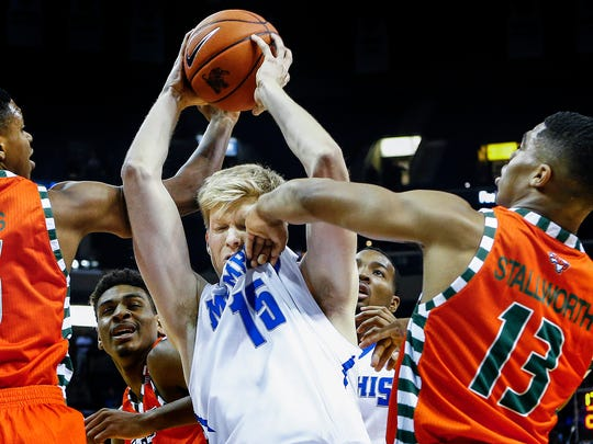 University of Memphis forward Chad Rykhoek (middle) takes a shot to the face from University of Texas Rio Grande Valley guard Lew Stallworth (right) after grabbing a rebound away from Walter Jones (left) during first-half action at FedExForum.