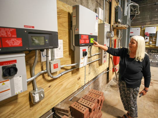Trisha Tull, with the Green Team at First Presbyterian Church, shows the control panels for the church's solar panels.  The church has three sets of solar panels.  The control panels are located in what was originally the coal room of the church.