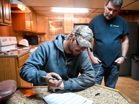 Working in the galley of the Lois Elaine, deckhand Rocky Rogers with his father Captain Josh Rogers fill out log sheets after finishing a beginning of the shift boat check Wednesday, October 18, 2017.
